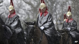 Members of the Household Cavalry pass by Buckingham Palace on their way to snow-covered ceremonial duties at Horse Guards Parade