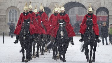 Troops of the Household Cavalry mounted division leave Horseguards parade after their ceremonial duty as it begins to snow