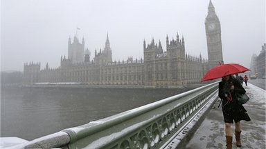 A woman carrying a red umbrella walks across Westminster Bridge in the snow