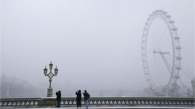 Tourists near the London Eye as it snows