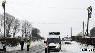Engineers repair a power cable that had fallen onto a road during a heavy snowfall near Narberth, west Wales