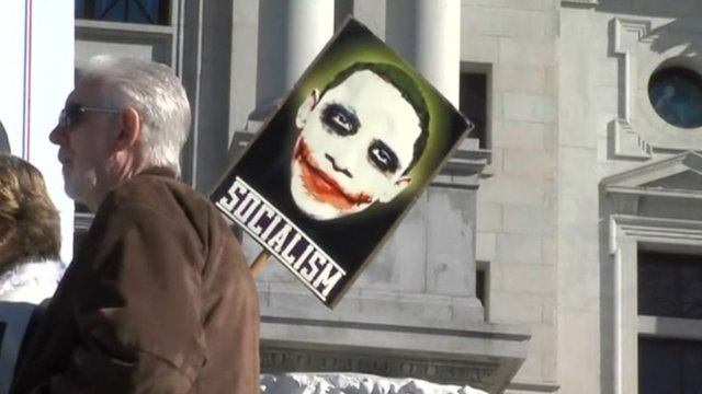 Protester hold sign showing Obama as 'the joker'