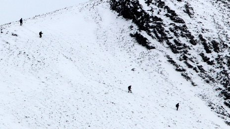 Climbers make their way down the mountains near Glencoe