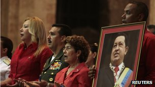 A man holds a picture of Hugo Chavez at a mass in Havana, Cuba