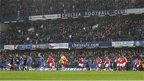 Chelsea and Arsenal players walk out for the start of their game at Stamford Bridge. It is snowing but the pitch is clear.