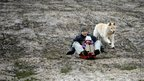 A man and his young daughter sledge down a muddy hill with a light covering of snow, chased by a large white dog