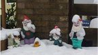 Four garden gnomes covered in snow outside a house