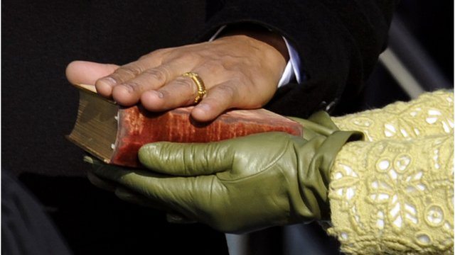 Obama's hand on a Bible held by Michelle Obama