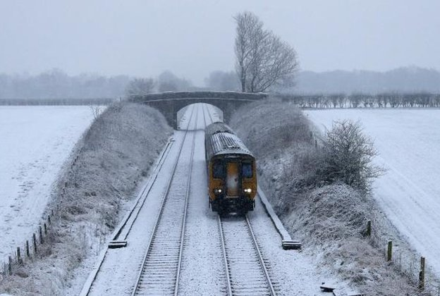 Train passes through snow covered fields near Manchester