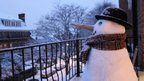 A snowman on a balcony looks out to the residential street. He is wearing a scarf and bowler hat and has a carrot for a nose.