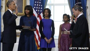 U.S President Barack Obama (L) takes the oath of office from US Supreme Court Chief Justice John Roberts (R) as First Lady Michelle Obama holds the Bible and daughters Malia and Sasha look on in the Blue Room of the White House on Sunday in Washington DC
