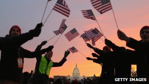 People wave American flags as people gather near the US Capitol building on the National Mall for the Inauguration ceremony in Washington DC on Monday