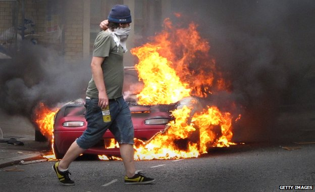 Masked man near burning car, 2011