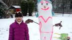 A snow woman sprayed with pink luminous paint.