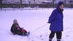 Two girls being pulled along on a sledge in the snow by their mother.