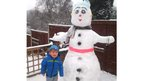 A boy stood next to an enormous snowman.