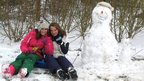 Two girls in the snow with their snowman.