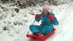 A girl rides her sledge down a road.