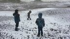 Three boys on a snow covered beach.