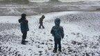 Three boys on a snow covered beach.