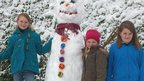 A tall snowman next to three girls.