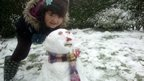 A girl standing beside her snowman.