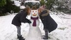 Two girls kissing a snowman on the cheek.