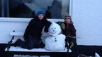 A snowman on a bench with two boys.