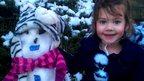 A girl sat beside her snowman.
