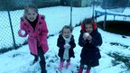 Three girls standing in a snowy garden holding snowballs. 