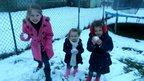 Three girls standing in a snowy garden holding snowballs.