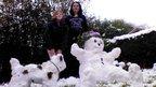 A snow girl and a snow dog.