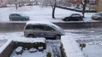 snow covers cars outside a house