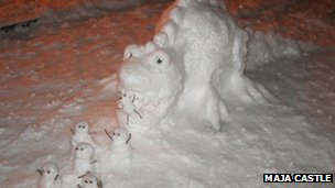 Snow dinosaur eats mini snowmen