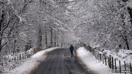 A man runs among the snow covered trees surrounding the grounds close to Stourhead
