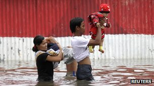 Parents carry their children through flood waters in Jakarta, Indonesia (18 Jan 2013)