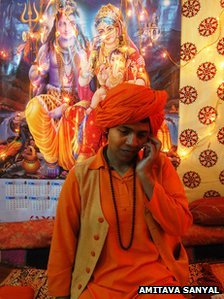 Devya Giri, leader of the new women's order, on a mobile phone in front of a picture of Hindu gods Shiva and Parvati
