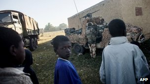 Malian children watch French soldiers