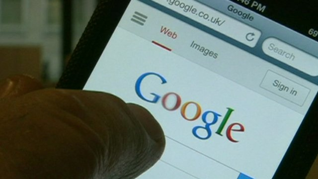 Finger pointing at Google search page on a smartphone
