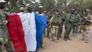 This handout picture taken on January 19, 2013 and released on January 22, 2013 by the French Army Communications Audiovisual office (ECPAD) shows French and Malian soldiers standing next to a man wearing a cloth made with the colors of the French national flag in Niono.