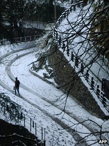 A man walks on a snow covered road after snowfall in the northern hill town of Shimla 