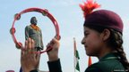 Girl playing a tambourine in front of Netaji Subhash Chandra Bose statue
