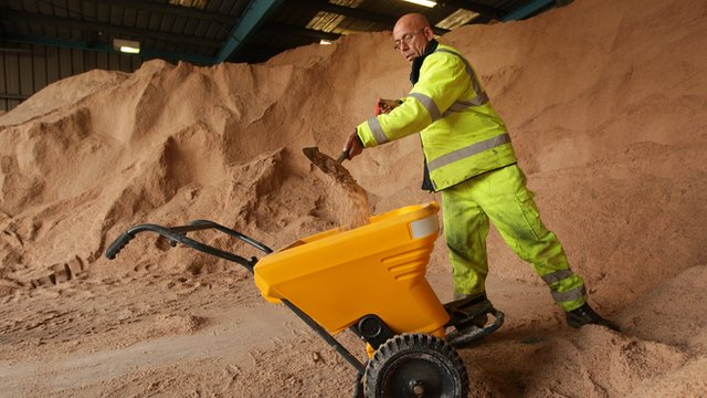Council worker filling a trolley with gritting salt