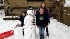Three children next to their snowmen.