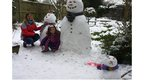 A lady and girl beside a snowlady, snowman and snowcat.