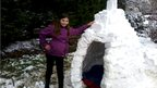 A girl stood beside an igloo.
