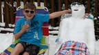 A boy on a sun lounger in sunglasses and shorts next to a snowman on a sun lounger.