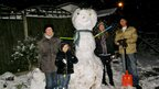 A family with an enormous snowman.