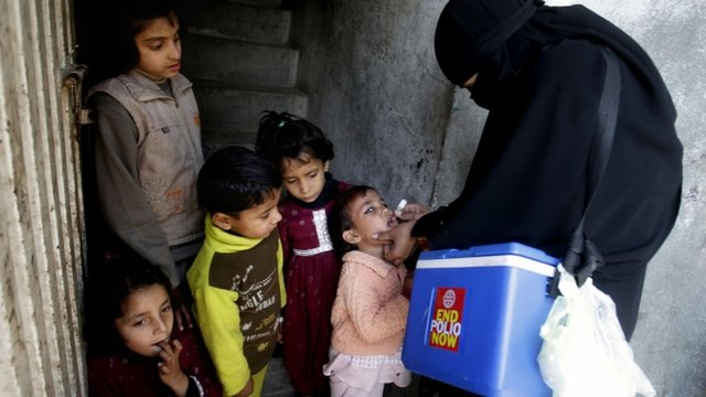 Pakistani health worker administering polio medication