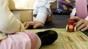 Adult playing with child at nursery